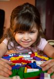 Cute child stacks building cubes sitting at table in nursery room royalty free stock images