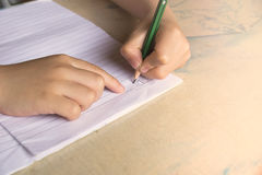 Close up Children are holding a pencil and writing. Royalty Free Stock Image