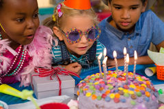 Close up of children looking at birthday cake Royalty Free Stock Photography