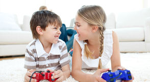 Close-up of children playing video games. Lying on the floor Royalty Free Stock Photo