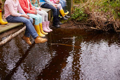 Close Up Of Children's Feet Dangling From Wooden Bridge stock photography
