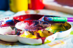 Close-up of childrens paint brush on paint palette. Close-up of children's paint brush on messy paint palette with bottles of paint in background Stock Photos