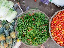 Close up of chili peppers, tomatoes, pineaples and some lettuce at outdoors in the street market in Hue, Vietnam.  stock photos
