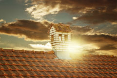 Close up chimney like a littl house on the roof in the evening sunset Royalty Free Stock Image