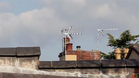 Close Up of Chimney Pots Television Aerials & Roof Top Tiles - Blue Sky Fuffy Clouds - Buidling Backgrounds stock footage