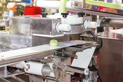Close up chinese or asian food steamed stuffed buns on automatic belt conveyor of food making machine in production line for high. Technology industrial royalty free stock photo
