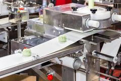 Close up chinese or asian food steamed stuffed buns on automatic belt conveyor of food making machine in production line for high. Technology industrial royalty free stock image