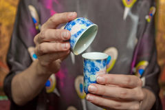 Close-up of chinese cup and bowl in hands Royalty Free Stock Photos