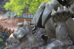 Close up of Chinese statute of baby dragon / lion in China. Close up of baby lion / dragon statue, playing with parent`s claw. Chinese mythology, baring teeth stock photos