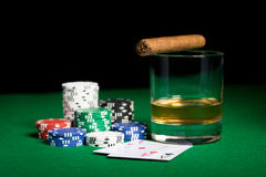Close up of chips, cards whisky and cigar on table Stock Photo