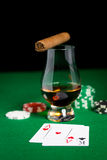 Close up of chips, cards whisky and cigar on table Stock Images