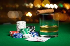 Close up of chips, cards whisky and cigar on table Royalty Free Stock Images
