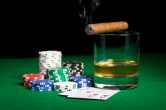 Close up of chips, cards whisky and cigar on table Stock Photography