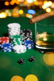 Close up of chips, dice, whisky and cigar on table Royalty Free Stock Photo