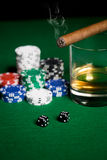 Close up of chips, dice, whisky and cigar on table Stock Image