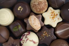 Close-up of chocolate candies in white, dark, and milk chocolate royalty free stock image