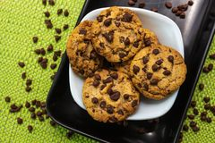 Close-up of chocolate chip cookies on colored tablecloths inside a black and white plate stock images