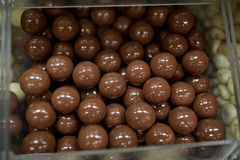 Close up of chocolate dragee candies in box. Food, junk-food, confectionery and unhealthy eating concept - close up of chocolate dragee balls in transparent Stock Images