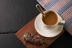 Close-up of chocolate eclair and coffee cup Royalty Free Stock Image