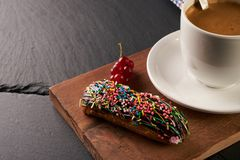 Close-up of chocolate eclair and coffee cup Stock Images