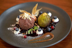 Close up of chocolate ice cream dessert on plate. Food, new nordic cuisine and sweets concept - close up of chocolate ice cream dessert with blueberry kissel Royalty Free Stock Photography