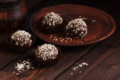 Close-up chocolate pralines with coconut on a dark rustic wooden table. Homemade sweets.. Selective focus stock photos