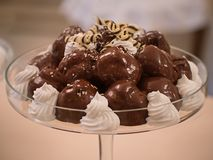 Close up chocolate profiterole filled with cream stock photography