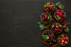 Close up of chocolate tartlets with chocolate cream, fresh strawberries, raspberries, blueberries, red currants and cherries. On black wooden background Royalty Free Stock Photo