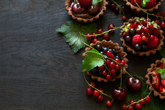 Close up of chocolate tartlets with chocolate cream, fresh strawberries, raspberries, blueberries, red currants and cherries. On black wooden background Stock Images