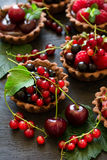 Close up of chocolate tartlets with chocolate cream, fresh strawberries, raspberries, blueberries, red currants and cherries. On black wooden background Stock Image