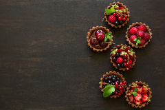 Close up of chocolate tartlets with chocolate cream, fresh strawberries, raspberries, blueberries, red currants and cherries. On black wooden background Royalty Free Stock Image