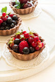 Close up of chocolate tartlets with chocolate cream, fresh strawberries, raspberries, blueberries, red currants and cherries. On white wooden background Royalty Free Stock Images