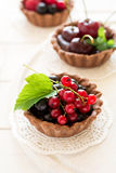 Close up of chocolate tartlets with chocolate cream, fresh strawberries, raspberries, blueberries, red currants and cherries. On white wooden background Royalty Free Stock Image