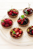 Close up of chocolate tartlets with chocolate cream, fresh strawberries, raspberries, blueberries, red currants and cherries Stock Images
