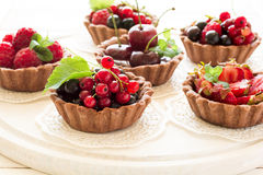 Close up of chocolate tartlets with chocolate cream, fresh strawberries, raspberries, blueberries, red currants and cherries. On white wooden background Royalty Free Stock Photo