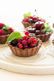 Close up of chocolate tartlets with chocolate cream, fresh strawberries, raspberries, blueberries, red currants and cherries. On white wooden background Stock Photos