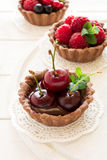 Close up of chocolate tartlets with chocolate cream, fresh strawberries, raspberries, blueberries, red currants and cherries. On white wooden background Stock Images