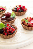 Close up of chocolate tartlets with chocolate cream, fresh strawberries, raspberries, blueberries, red currants and cherries. On white wooden background Royalty Free Stock Photos