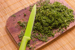 Close-up of chopped dill on a board with a knife. Knife resting on a wooden board with freshly chopped dill Stock Images