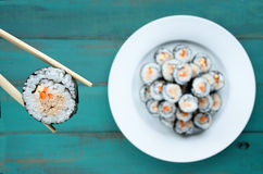 Close up of chopsticks holds sushi maki gunkan roll over a plate Stock Photos