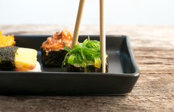 close up of chopsticks taking portion of sushi roll on the table Royalty Free Stock Image