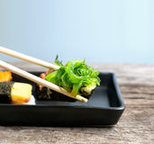 close up of chopsticks taking portion of sushi roll on the table Stock Image