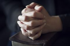 Folding Hands over a Bible Royalty Free Stock Image