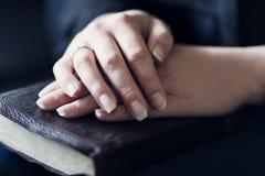 Women Holding Hands on a Bible Stock Photos