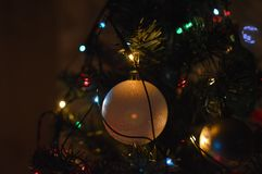 Close-up of a Christmas bauble ornament and colorful lights on a fir tree Royalty Free Stock Image
