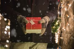Close up of man hand with gloves, with Christmas present or gift stock photo
