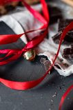Small gold jingle bells with satin red ribbon on dark texture table stock photos