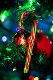 Close up of a Christmas decoration,. Close up of a red, white and green striped candy cane, bobbles and christmas tree royalty free stock images