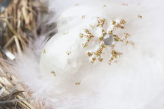 Close-up of christmas decoration from white decorative celluloid mittens with fluffy bird feathers in nest. Festive background , backdrop Stock Photography