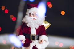 Close-up of Christmas decorative Santa Claus toy. Bokeh lights.  Stock Photo